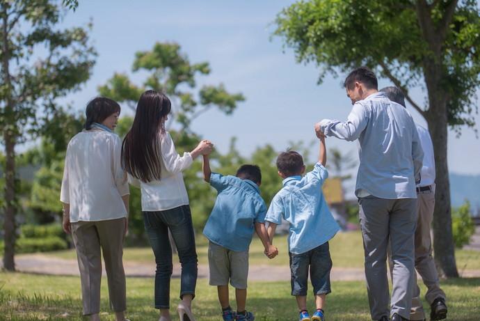 家族が手をつないで歩いている画像