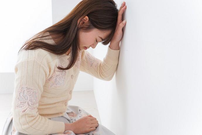 壁に手を付いている女性